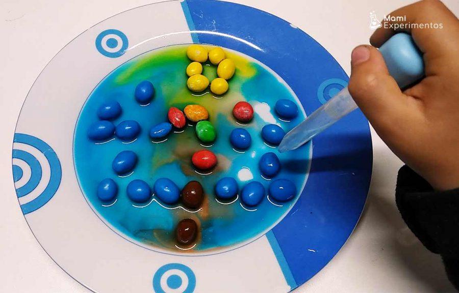 Agua coloreada por los caramelos de colores en creación de navidad