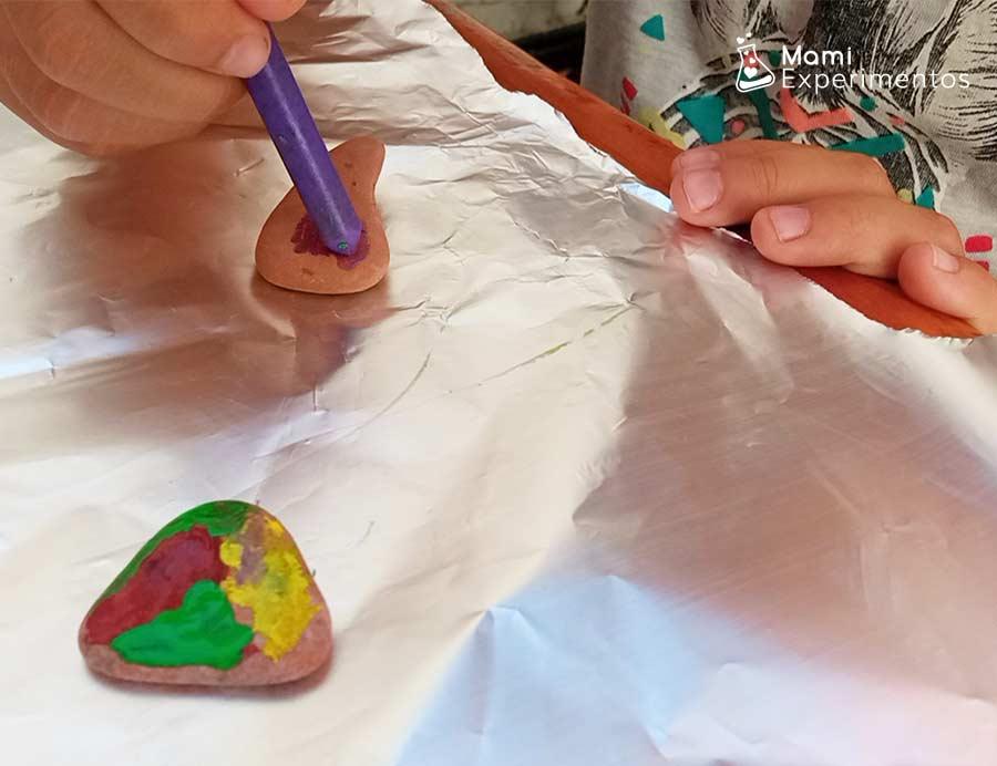 Arte con las piedras calientes y ceras de colores