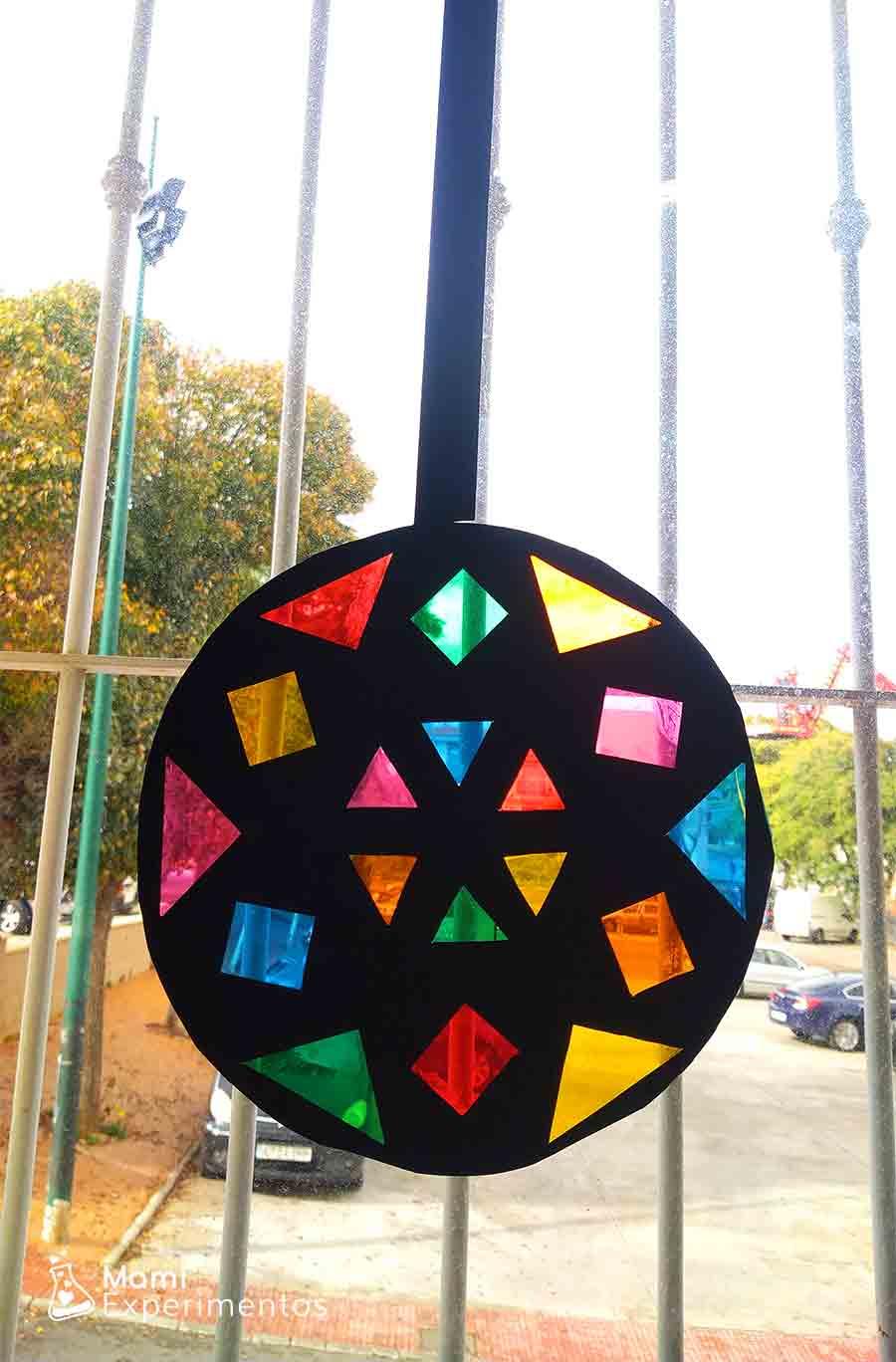 Bola de navidad con papeles de colores en ventana