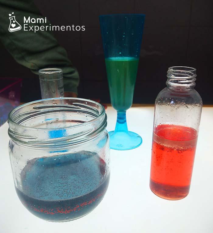 Botes varios con agua coloreada en mesa de luz
