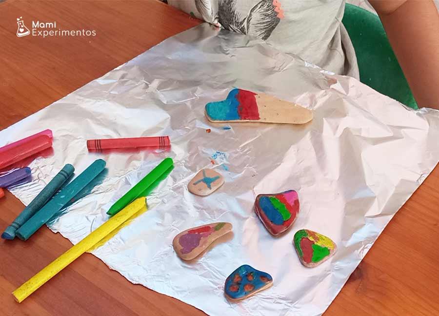 Ceras de colores derretidas en contacto con piedras calientes