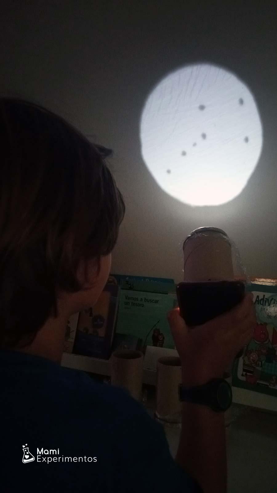 Constelaciones proyectadas en la pared con linterna y rollos de papel