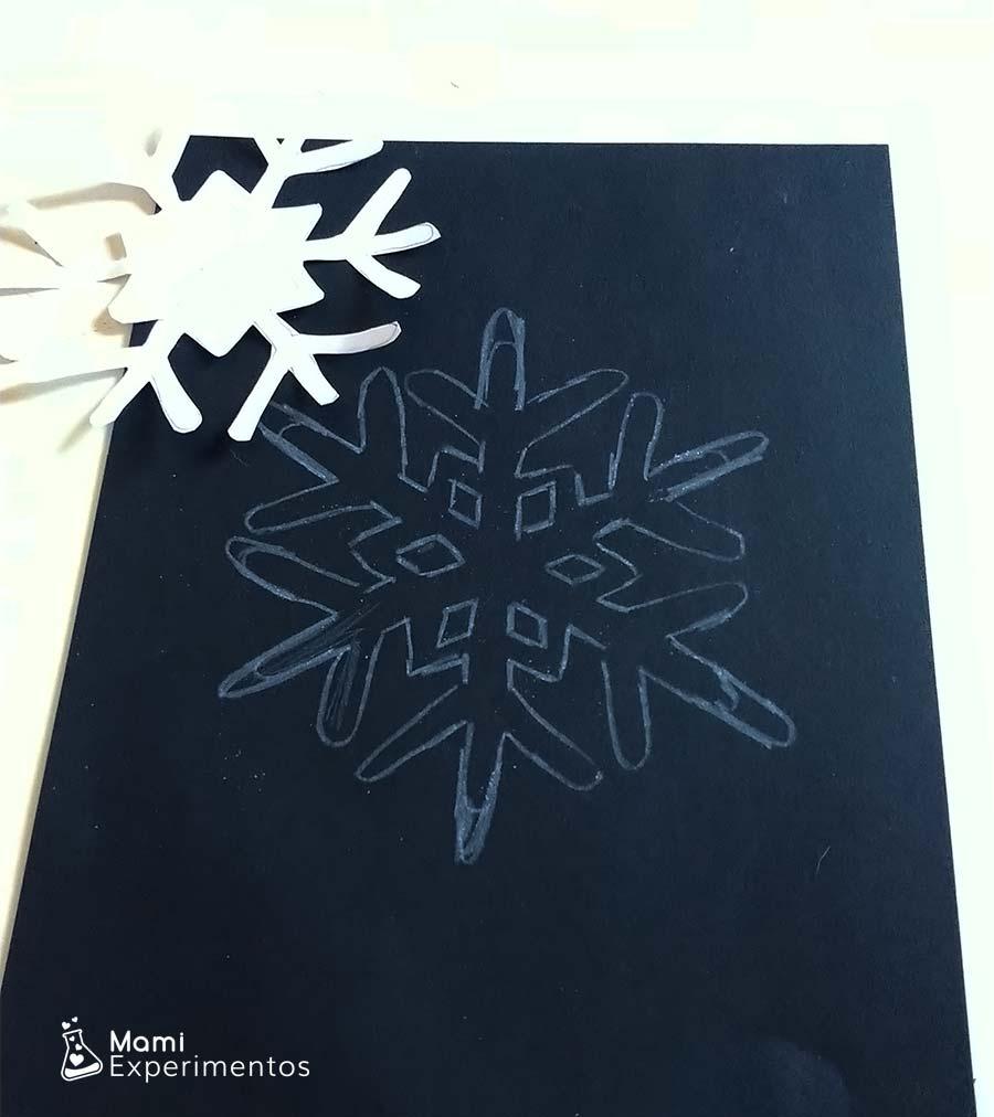 Copo de nieve dibujado en cartulina negra