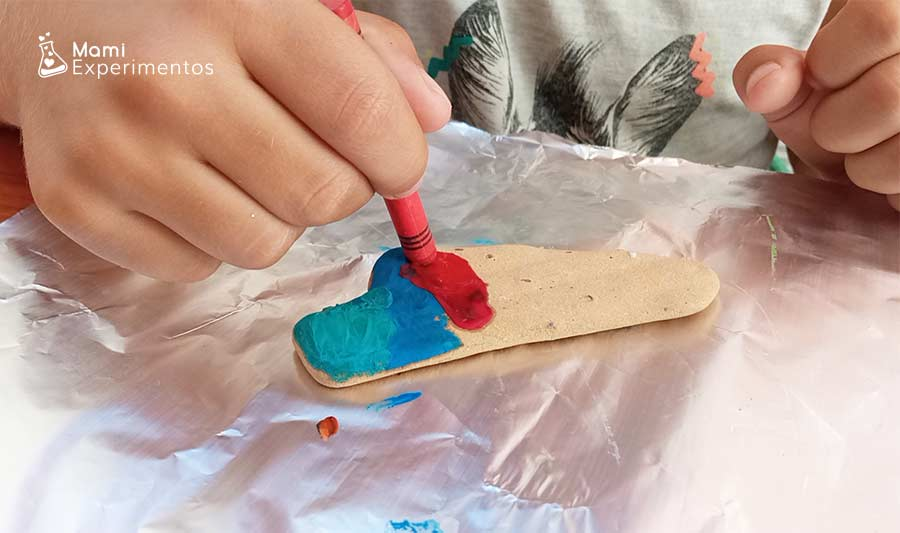 Decorando con lápices de ceras en piedras calientes viendo como se derriten los colores