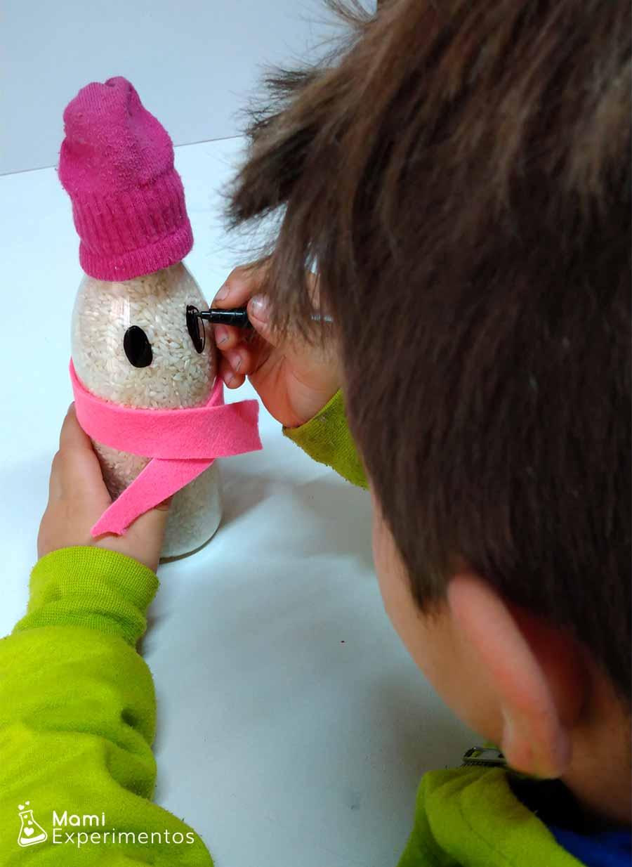 Decorando ojos en botella sensorial de muñeco de nieve con arroz