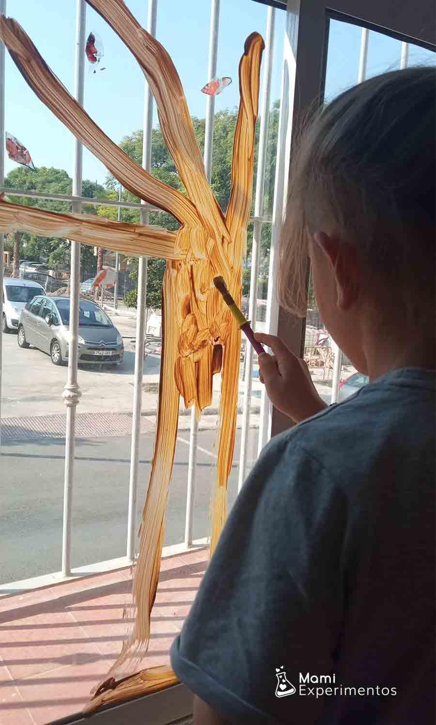 Decorando ventana con árbol de otoño y hojas hechas con ceras derretidas