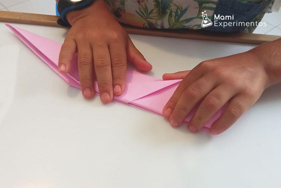 Doblar papel rosa para crear avión de papel que vuela