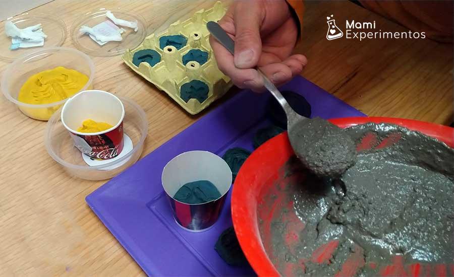 Echando cemento en moldes de plastilina para crear fósiles