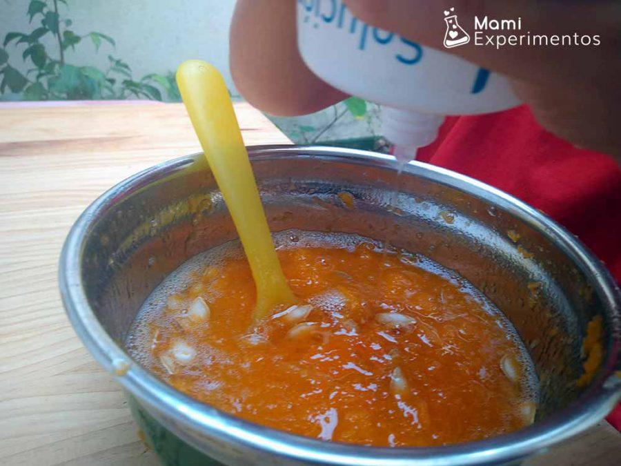 Echando líquido de lentillas para hacer nuestro slime de calabaza