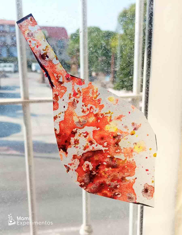 Hojas de otoño hechas con ceras de colores derretidas decorando ventanas