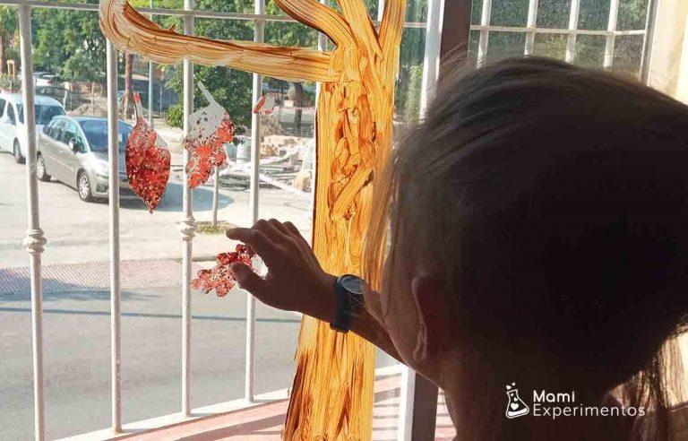 Hojas de otoño hechas con ceras de colores derretidas en forro de plástico decorando ventanales