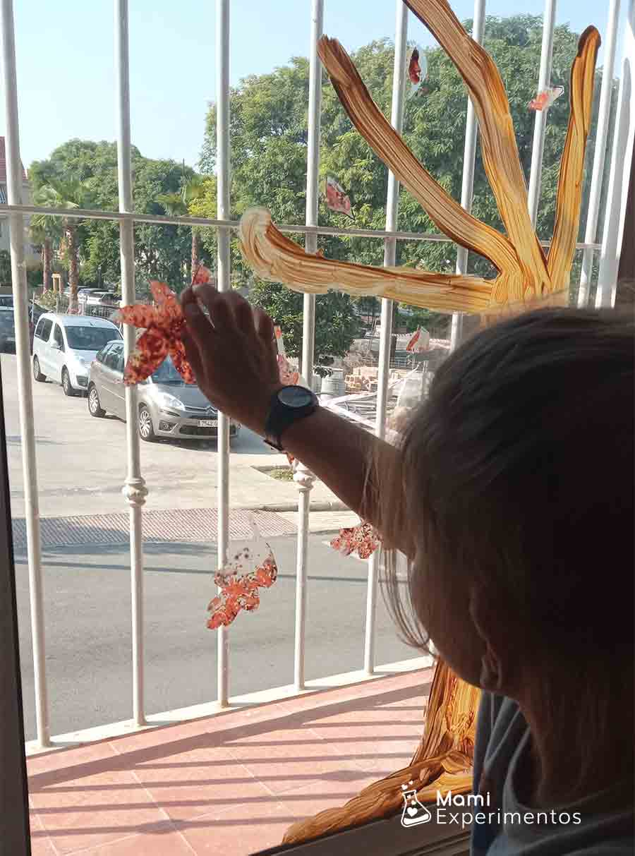Hojas de otoño realizadas con ceras derretidas en forro de plástico en ventanal