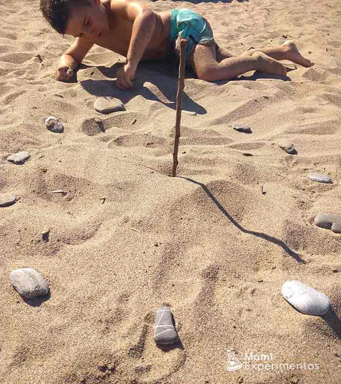 Jugar y aprender la hora con un reloj de sol en la playa