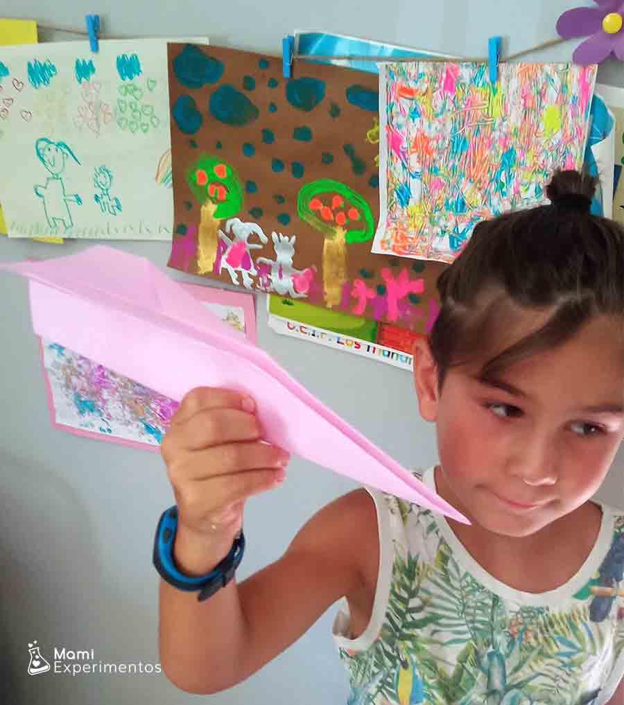 Lanzando avión de papel rosa física con aviones de papel