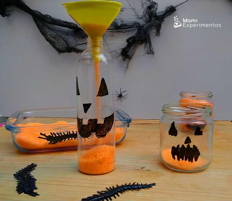 Llenando con embudo calabazas halloween con sal teñida naranja
