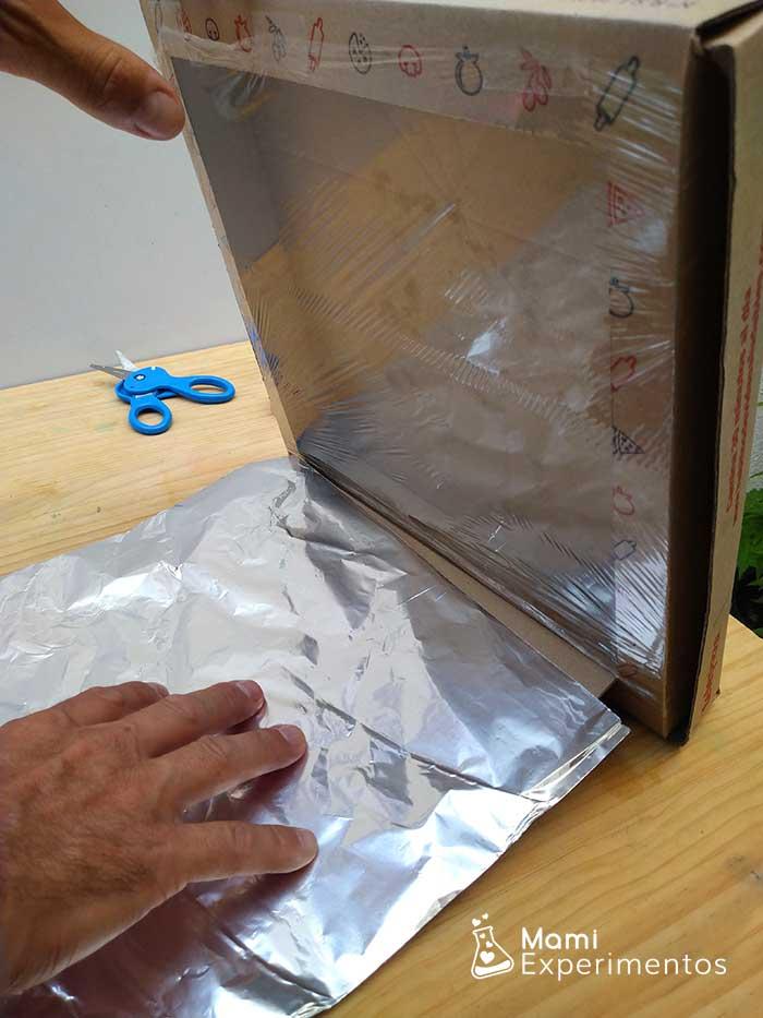 Papel aluminio en tapadera para que refleje sol en horno solar