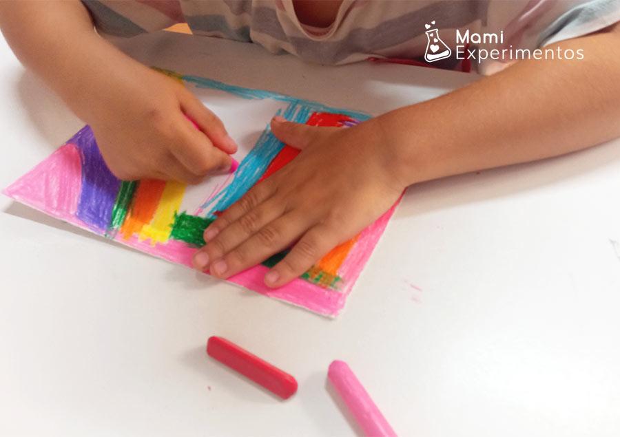 PIntando cartulina blanca con ceras de colores para arte en el día de las familias