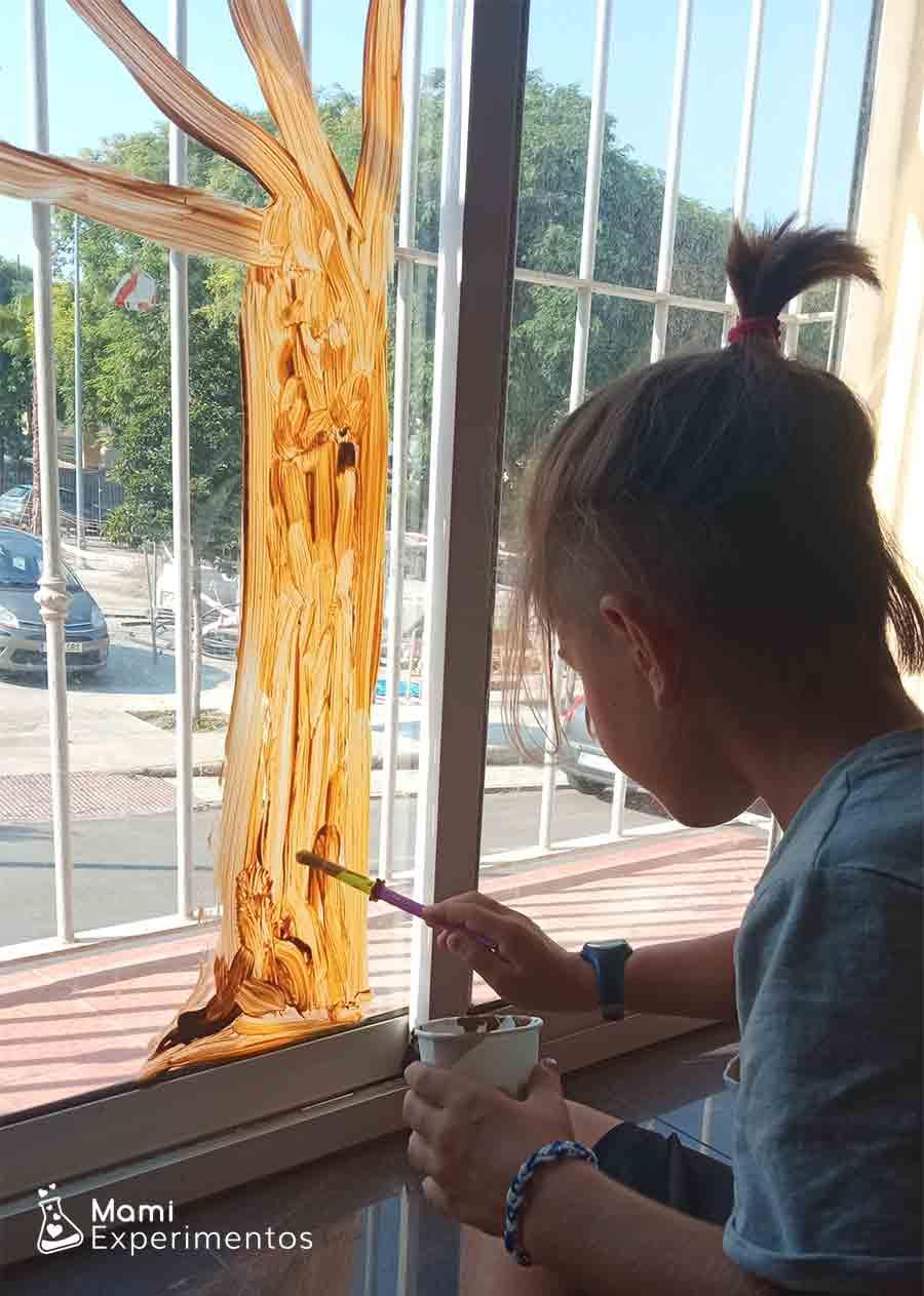 Pintando con témperas árbol de otoño en ventanal para actividad de hojas de ceras derretidas otoñales