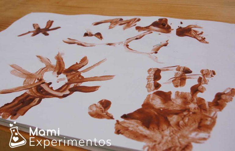 Estampando la mano en la pintura de chocolate
