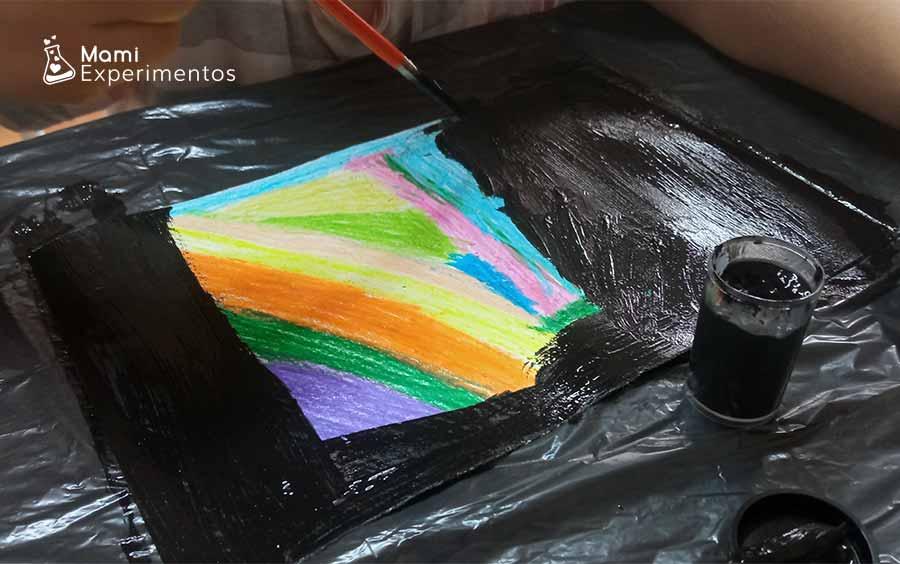 Pintar con témpera negra encima de las ceras de colores creación artística en el día de las familias