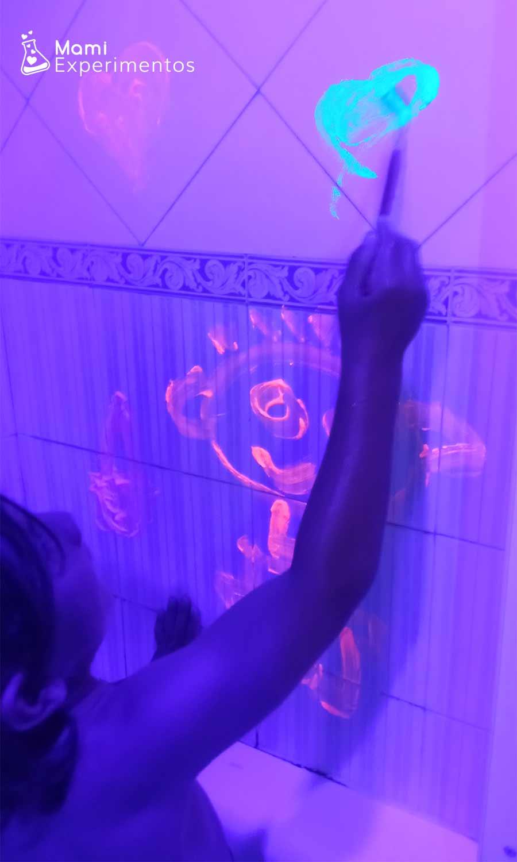 Pintar en los azulejos del baño con pintura fluorescente y disfrutar la luz negra