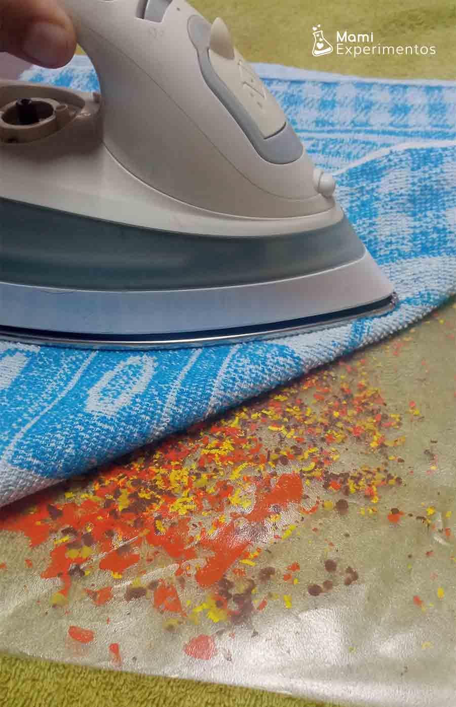Planchar forro relleno de ceras de colores con un trapo encima para actividad hojas de otoño