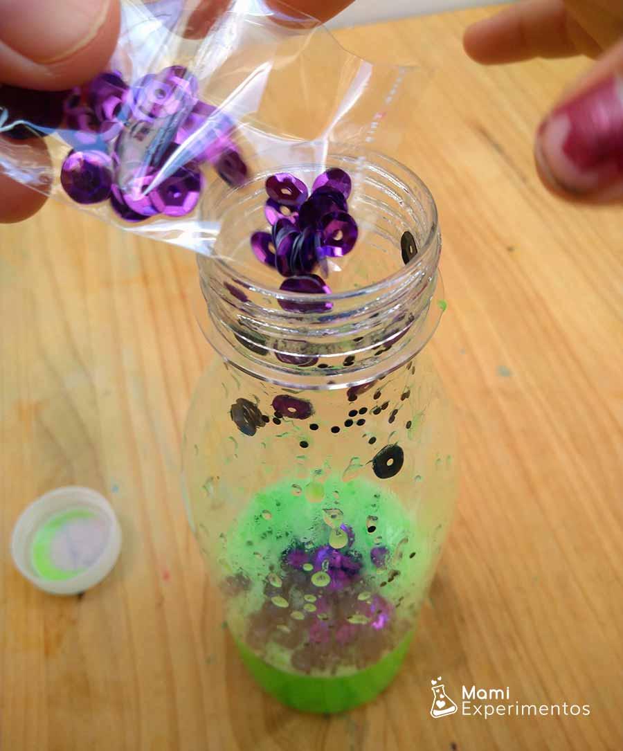 Decorando botella sensorial halloween con lentejuelas moradas