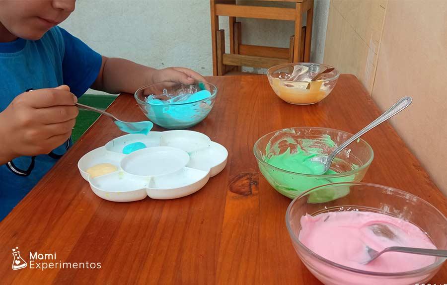 Preparando en recipiente pintura de yogur no tóxica de colores para bebés