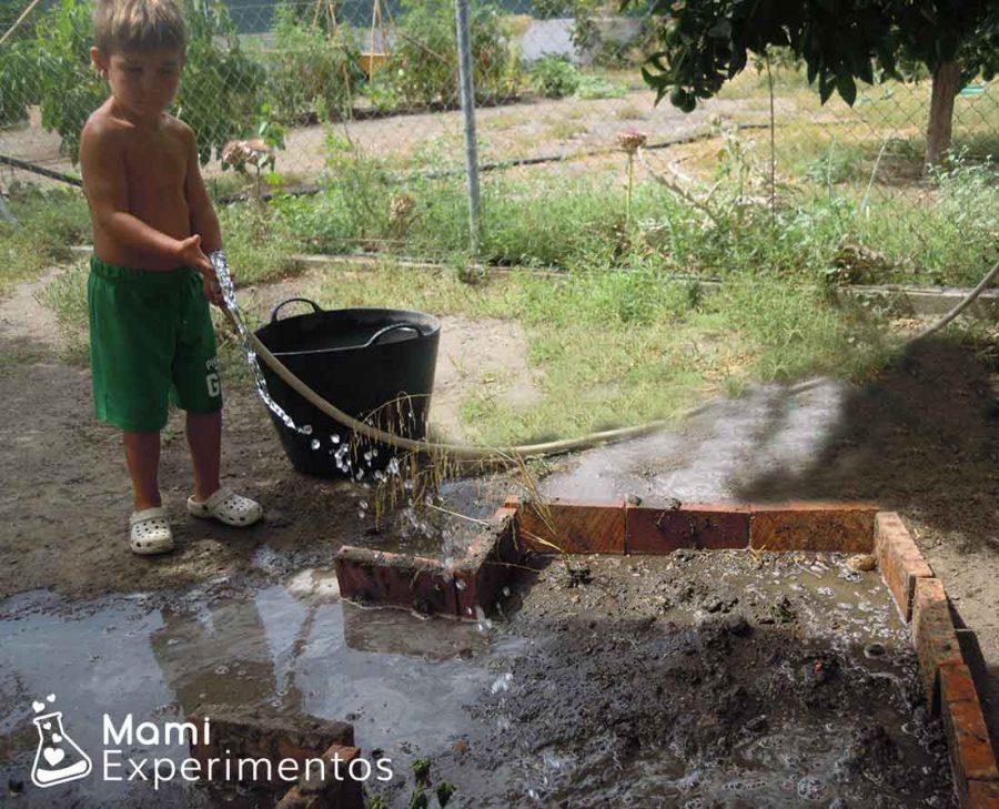 Echando agua a la tierra para formar barro