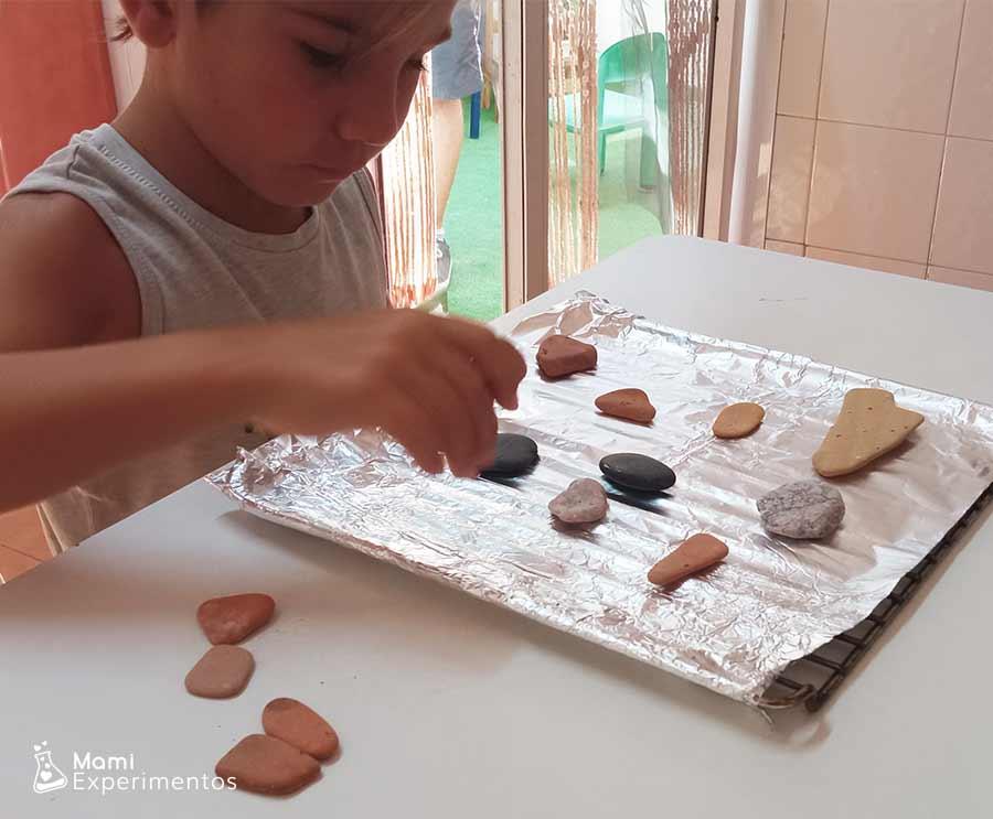 Preparando piedras en bandeja de horno para calentar y decorar con ceras