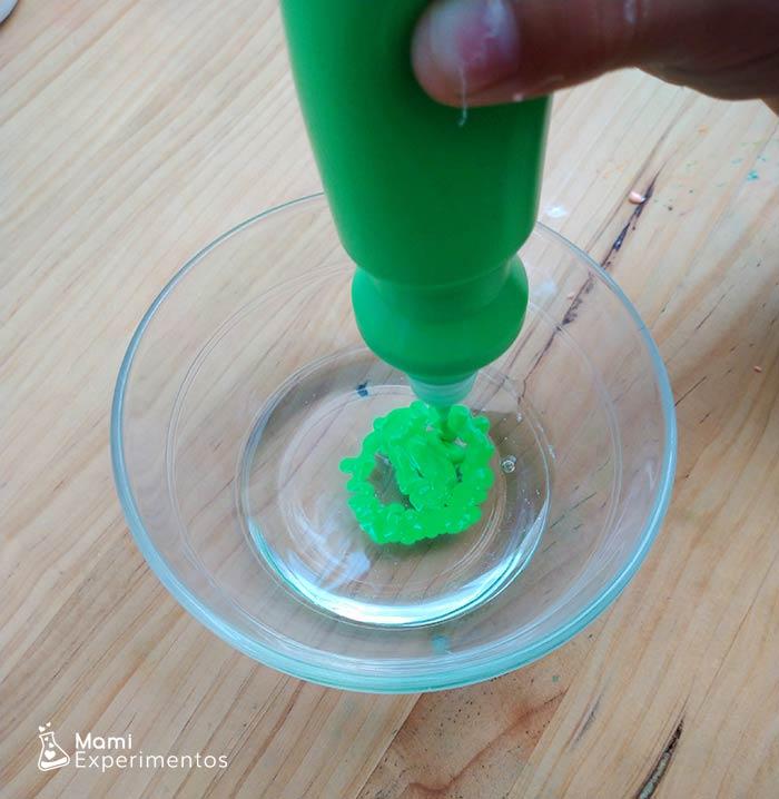 Preparando slime verde fluorescente para jugar con luz negra