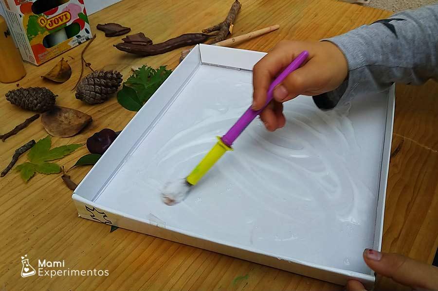 Preparando tapa de cartón con cola blanca para arte otoño