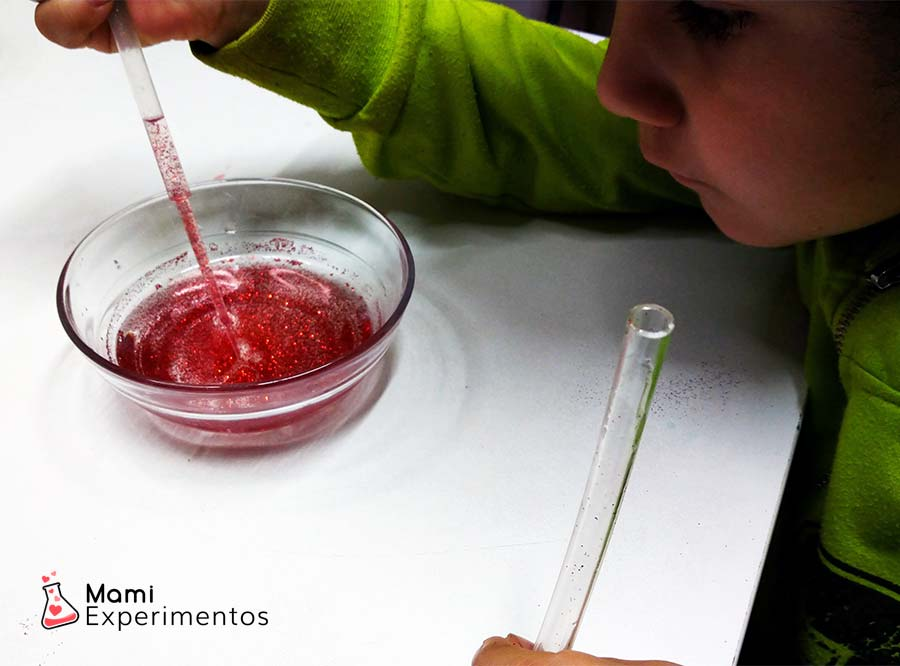 Preparando tubo sensorial con agua tintada de rojo y purpurina