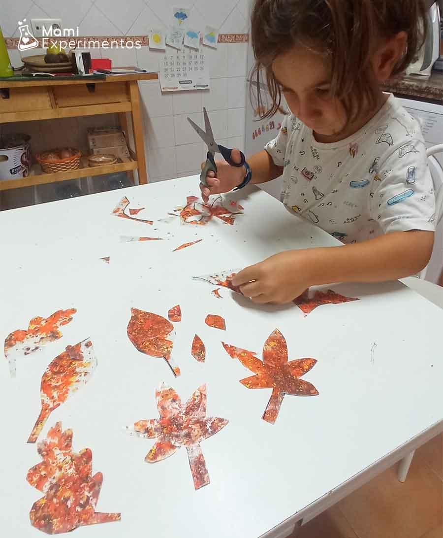 Recortando hojas de otoño hechas con forro relleno de ceras derretidas de colores otoñales