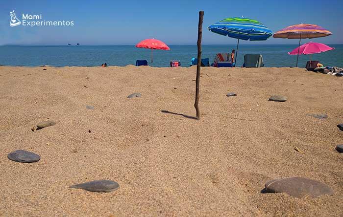 Reloj de sol con arena de la playa y piedras