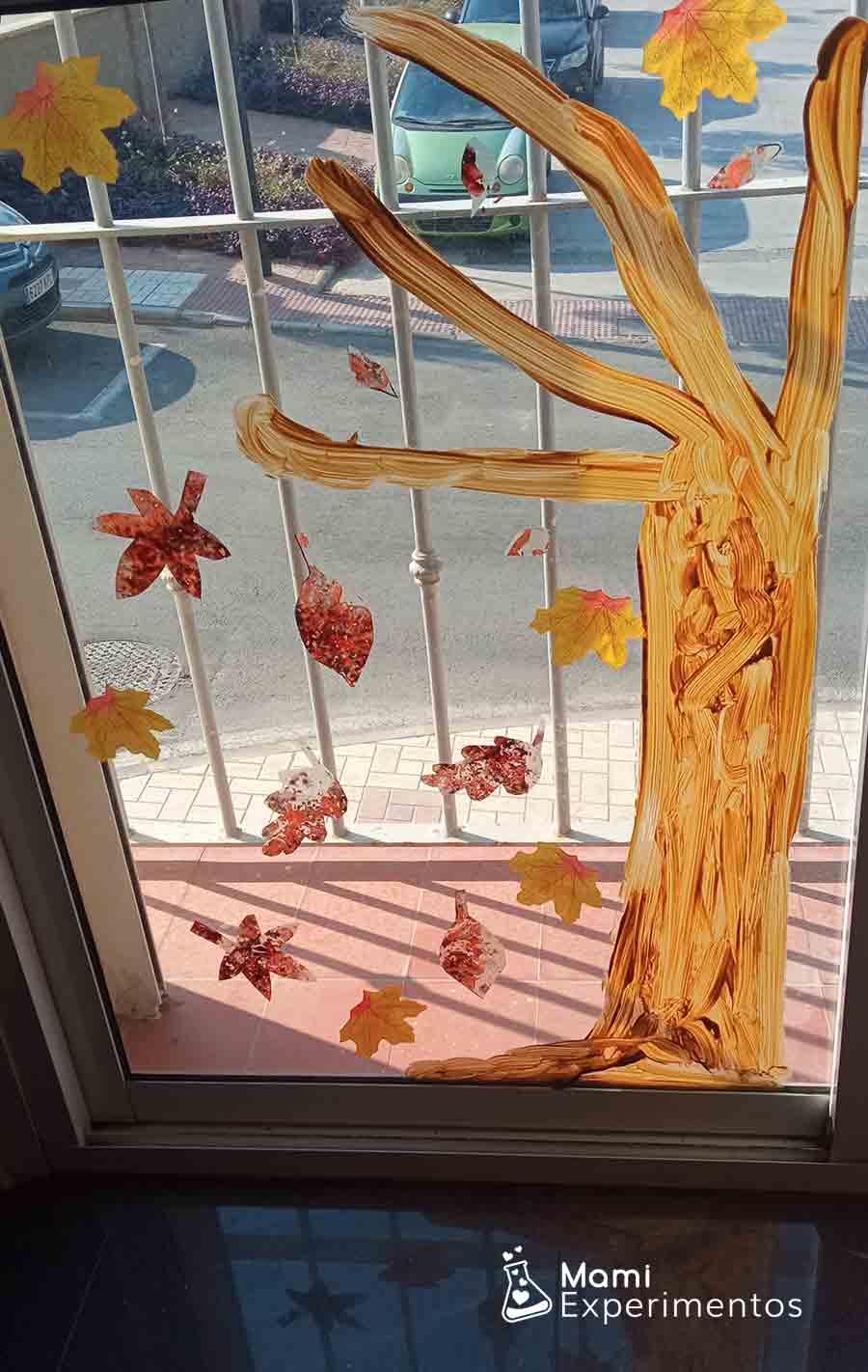 Resultado actividad sensorial de las hojas de otoño hechas con ceras de colores derretidas en forro de plástico adornando ventanal