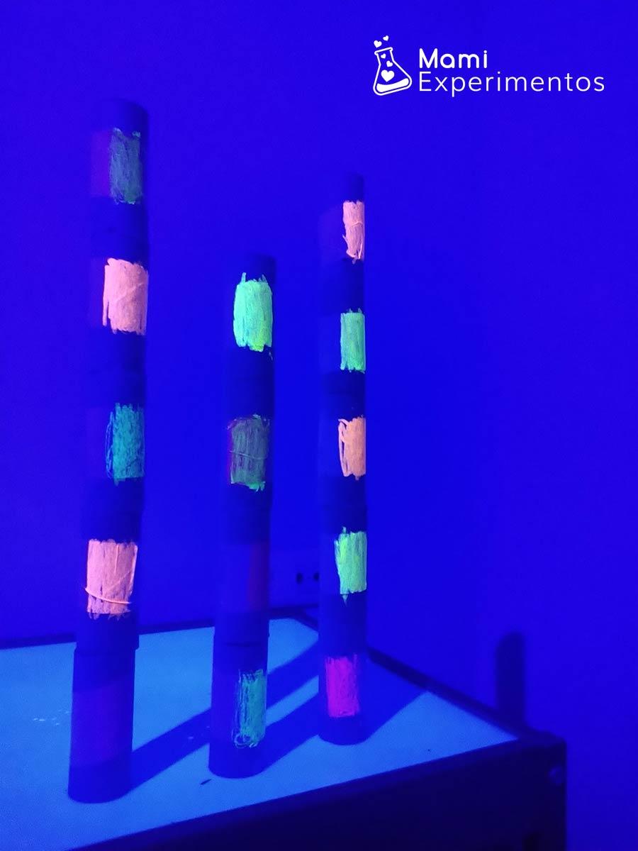 Torres de rollos de papel pintados fluorescentes y luz negra