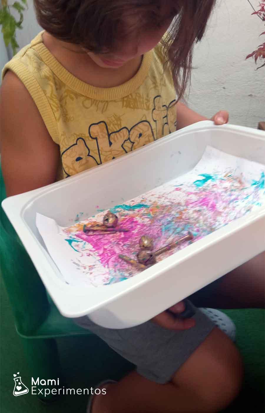 Varita magnética debajo de bandeja y pintando con objetos metálicos